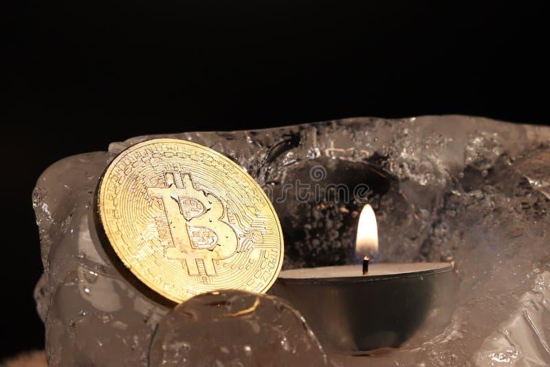 Nieuwjaar` s decoratie Bitcoin daalde in het ijs en opgehelderd door de vlam van een kaars tegen de achtergrond van Kerstboom royalty-vrije stock fotografie