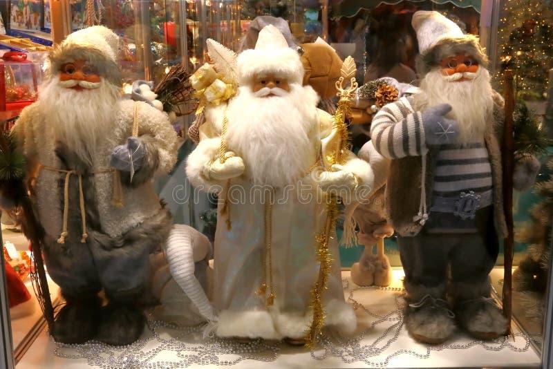 Nieuwjaar ` s en Kerstmis Drie Santa Claus in het winkelvenster o royalty-vrije stock foto's