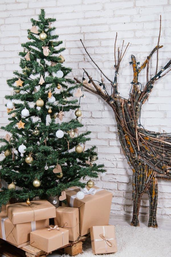 Nieuwjaar` s plaats in de studio met een hert, met een Kerstboom wordt verfraaid, giften, een mand van kegels die stock fotografie