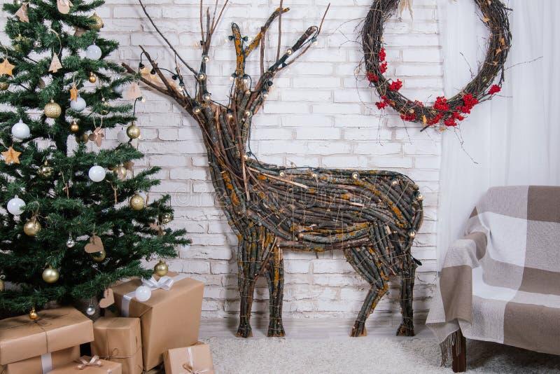 Nieuwjaar` s plaats in de studio met een hert, met een Kerstboom wordt verfraaid, giften, een mand van kegels die royalty-vrije stock afbeelding