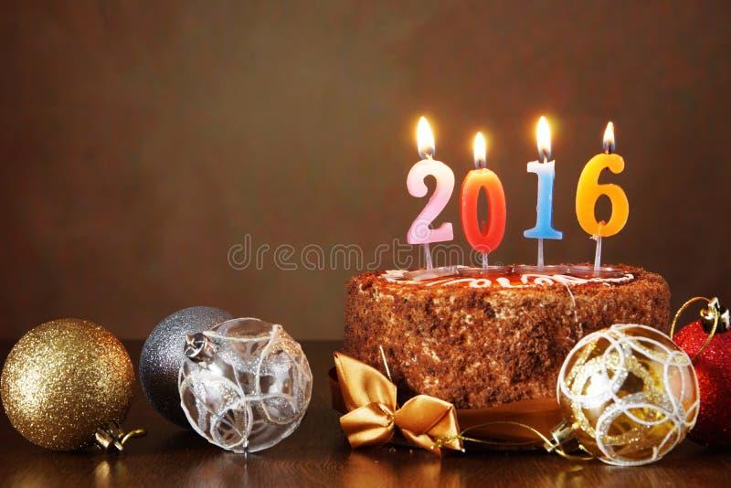 Nieuwjaar 2016 stilleven Chocoladecake en decoratieve boomballen stock afbeelding