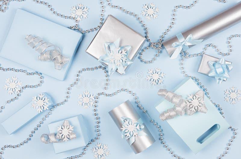 Nieuwjaarachtergrond - blauwe en zilveren metaal de giftdozen van de elegantie zachte pastelkleur met linten, sneeuwvlokken, boge stock afbeeldingen