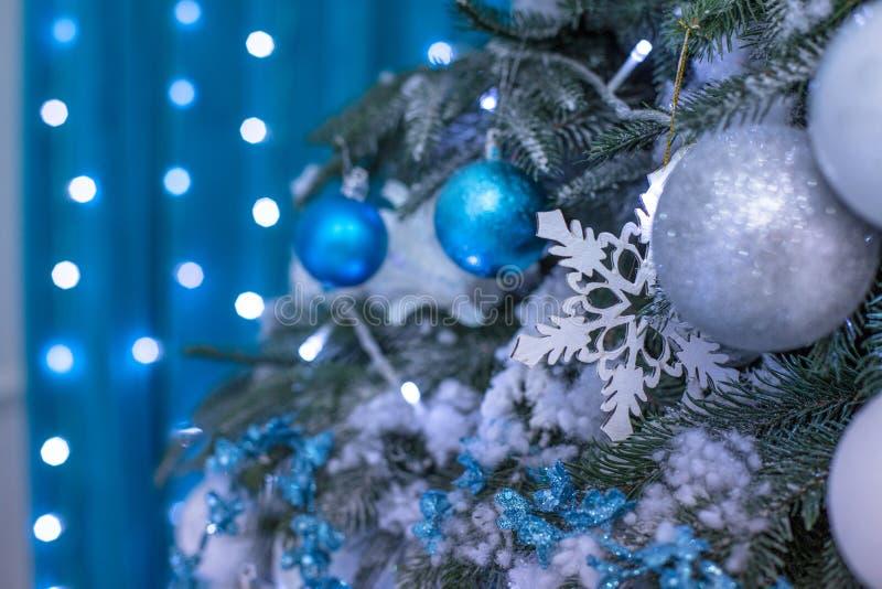 Nieuwjaarboom met blauw speelgoed wordt verfraaid - giften en ballen die achtergrond van onduidelijk beeld de Blauwe bokeh voor K stock foto