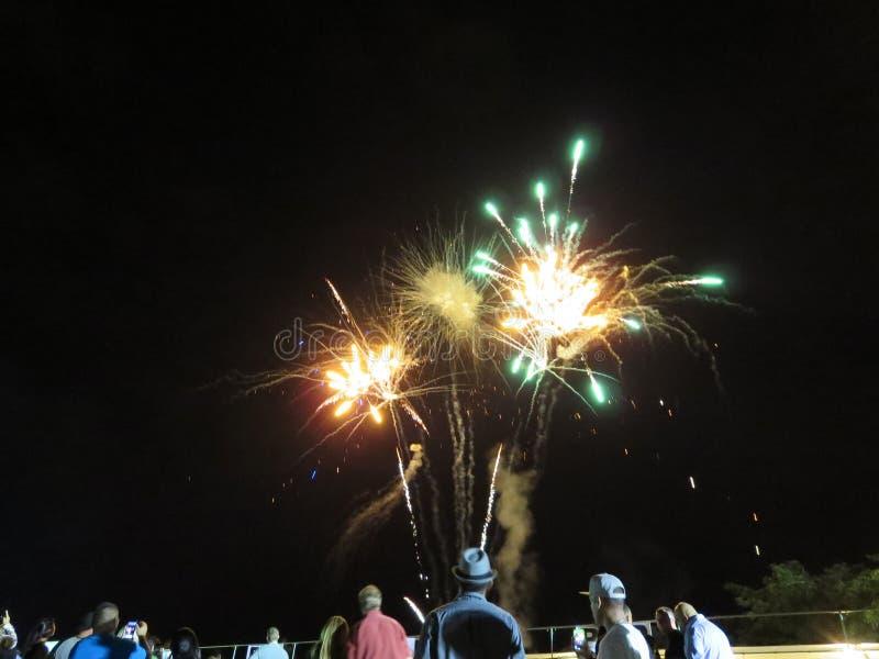 Nieuwjaren Vuurwerk in de lucht als vertoning die van het mensenhorloge is gebarsten bij royalty-vrije stock foto