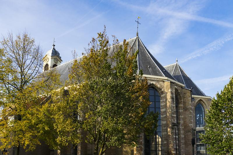 Church called Nieuwkerk in Dordrecht, The Netherlands. Nieuwkerk church in Dordrecht, Holland. With green trees against blue sku royalty free stock image