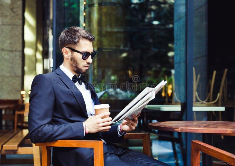 Nieuws en Koffie Jonge zakenman die het ochtenddocument lezen, drinkend koffie in een gebouw van het koffiebureau Zoete croissant royalty-vrije stock fotografie