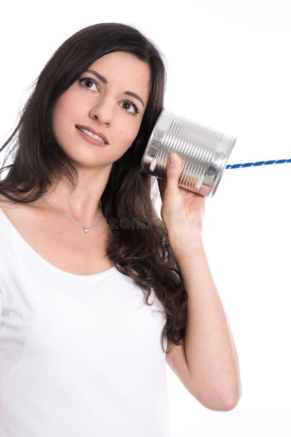 Nieuws en mededeling: jonge vrouw die aan telefoon i luisteren van het tinblik stock fotografie