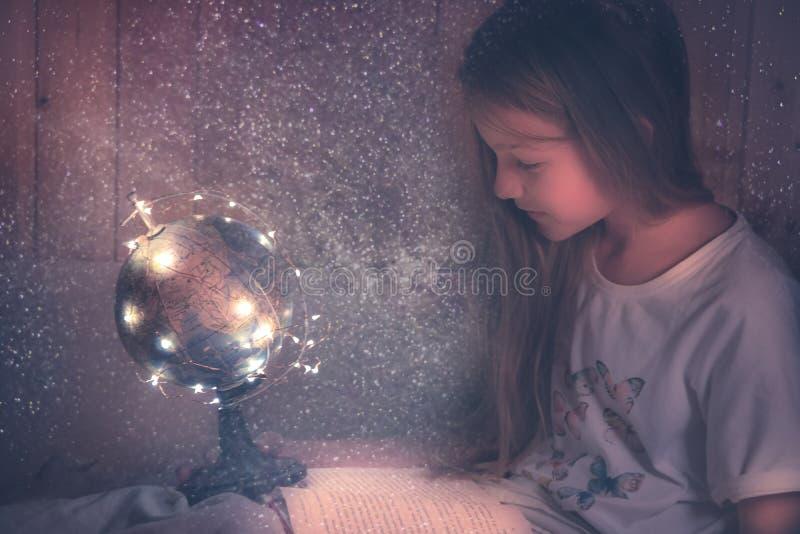 Nieuwsgierig bewonderend jong geitjemeisje die met boek in bed over ruimte en heelal het onderwijs van de de nieuwsgierigheidsken royalty-vrije stock afbeelding