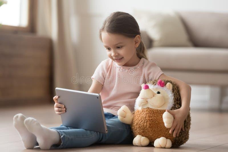 Nieuwsgierig kindmeisje die pret hebben die digitale tablet gebruiken die stuk speelgoed omhelzen royalty-vrije stock afbeeldingen
