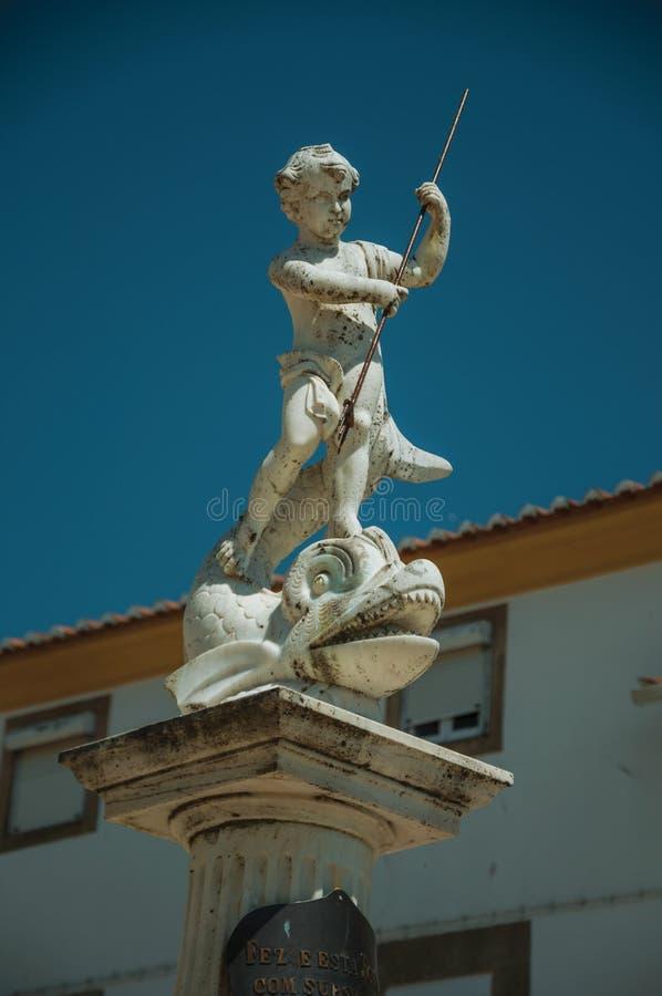 Nieuwsgierig marmeren standbeeld bovenop pijler stock afbeelding