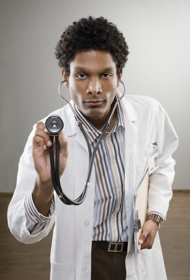 Nieuwsgierige arts in de holdingsstethoscoop van de laboratoriumlaag stock fotografie