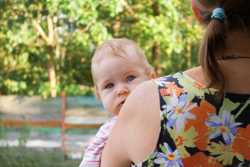 Nieuwsgierige baby die babe van achter de schouder van de moeder piepen royalty-vrije stock fotografie
