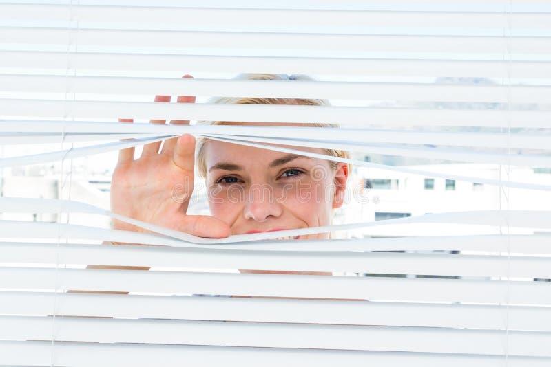Nieuwsgierige blondevrouw die door jaloezie kijken royalty-vrije stock afbeeldingen