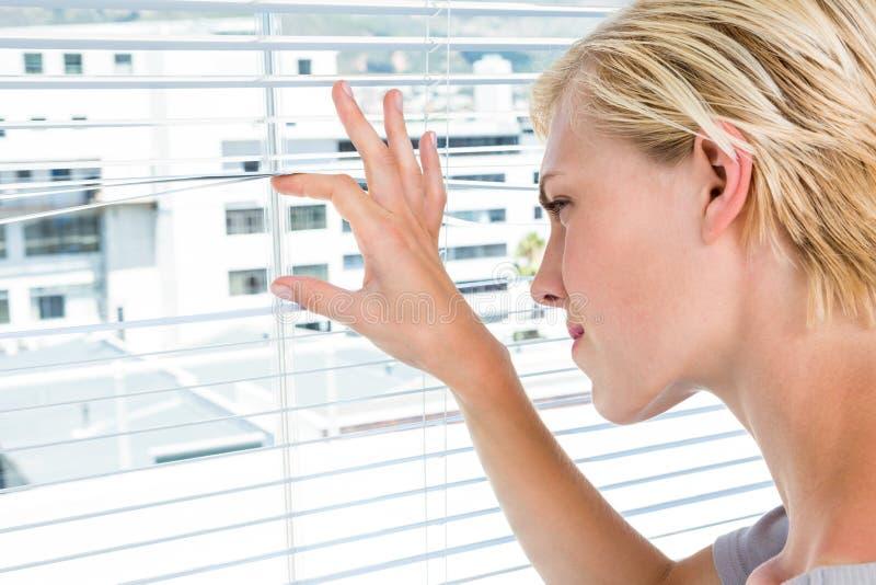 Nieuwsgierige blondevrouw die door jaloezie kijken stock foto's