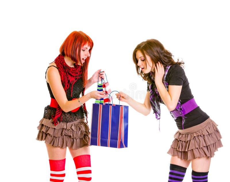 Nieuwsgierige charmante meisjes die het winkelen zak bekijken royalty-vrije stock afbeeldingen