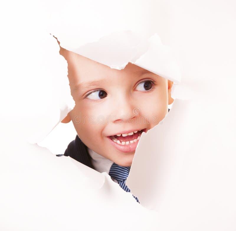 Nieuwsgierige glimlachende kleine spion stock fotografie