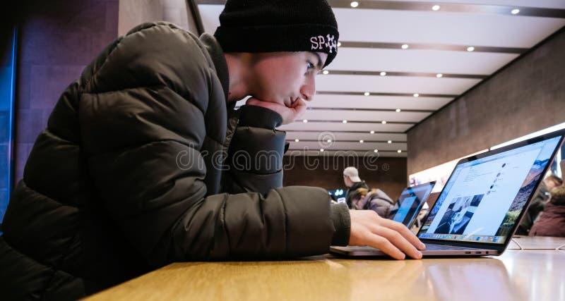 Nieuwsgierige jonge jongenslezing op pro de retinalaptop van Apple MacBook stock foto's