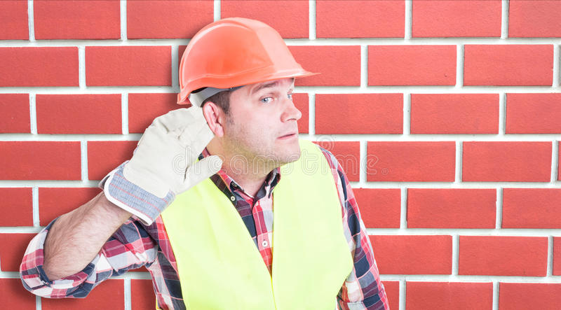 Nieuwsgierige mannelijke bouwer die het nieuws luisteren stock foto