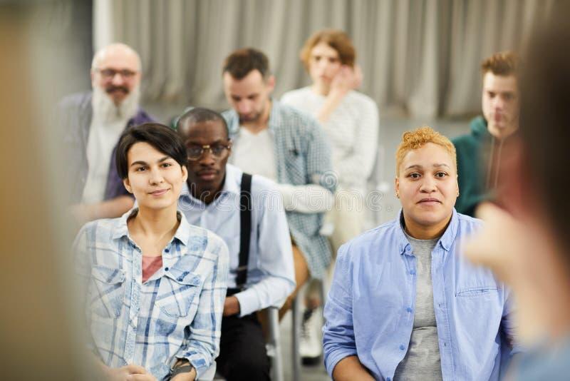 Nieuwsgierige mensen die aan spreker luisteren stock foto