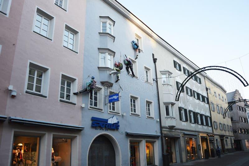 Nieuwsgierige voorgevelklimmer op een huisvoorzijde als winkel die in de Bruneck-voetgangers streek, Bruneck, Italië adverteren stock foto's