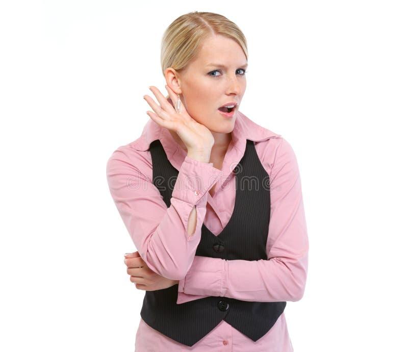 Nieuwsgierige vrouw die iets probeert te horen stock fotografie