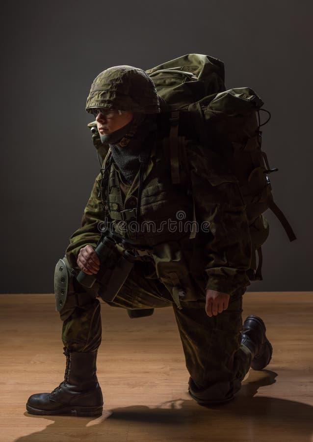 Nieuzbrojona kobieta z kamuflażem na jeden kolanie Młody żeński żołnierz obserwuje z lornetkami i plecakiem Wojna, wojskowy, wojs fotografia stock