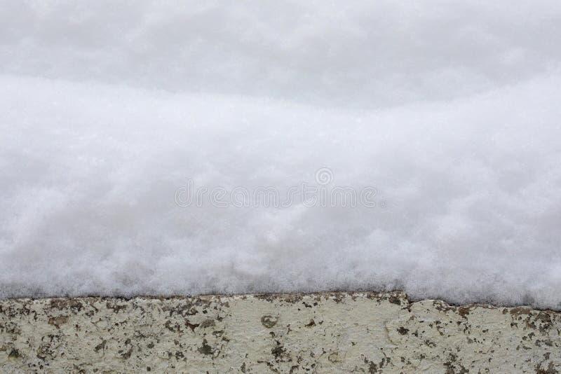 Nieve acumulada por la ventisca en el alféizar Fondo natural del invierno de la textura de la nieve foto de archivo