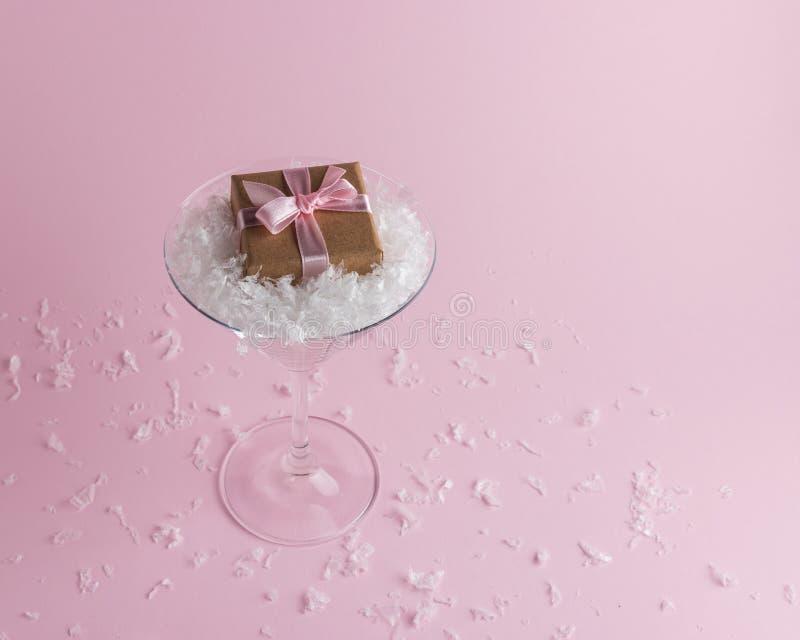 Nieve con la caja de regalo en el vidrio de martini en fondo rosado en colores pastel Concepto de la Navidad m?nima o del A?o Nue fotografía de archivo