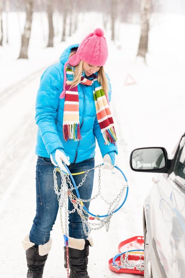 Nieve de la mujer que se coloca con los encadenamientos de neumático de coche imagen de archivo libre de regalías