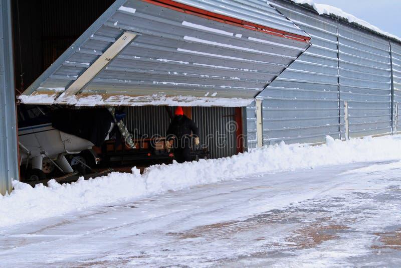Nieve de la puerta del hangar del aeropuerto de la abertura del hombre fotos de archivo libres de regalías