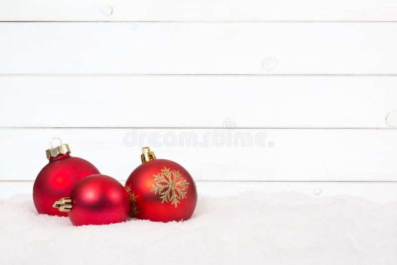Nieve de madera de la tarjeta de la decoración del fondo de las bolas rojas de la Navidad imagenes de archivo