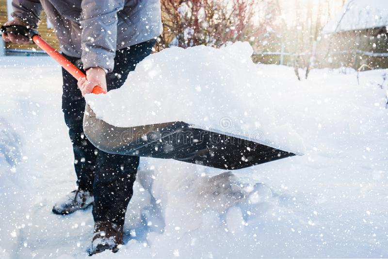 Nieve de vaciamiento del hombre por la pala después de nevadas outdoors imagen de archivo
