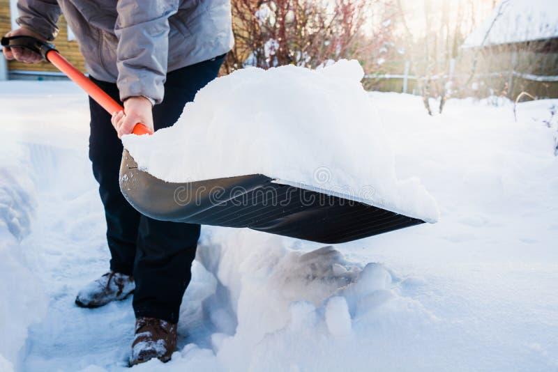 Nieve de vaciamiento del hombre por la pala después de nevadas outdoors imagenes de archivo