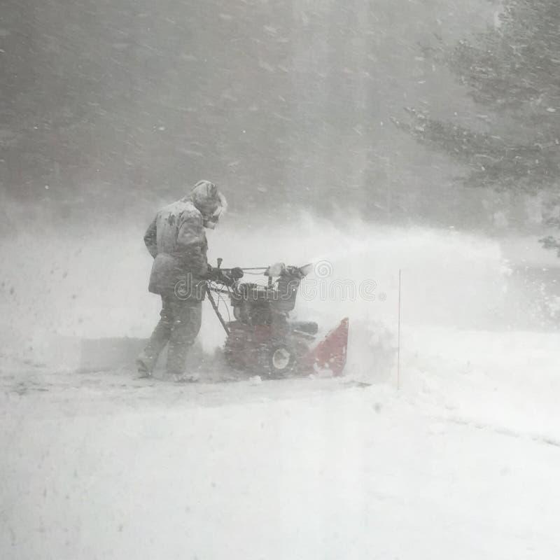 Nieve del claro del hombre durante una ventisca imagenes de archivo