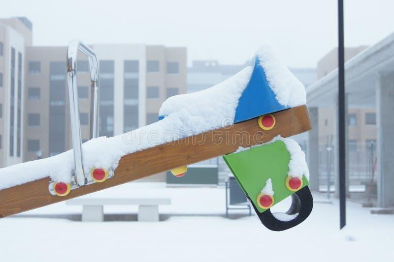 Nieve en el balancín, caballo. imagen de archivo