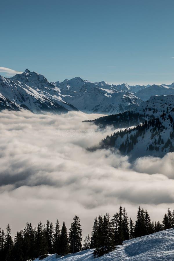 Nieve en el top de las montañas y de la niebla abajo del valle foto de archivo libre de regalías