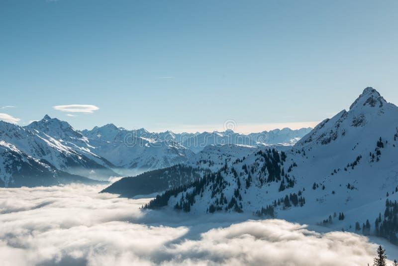 Nieve en el top de las montañas y de la niebla abajo del valle imagen de archivo libre de regalías