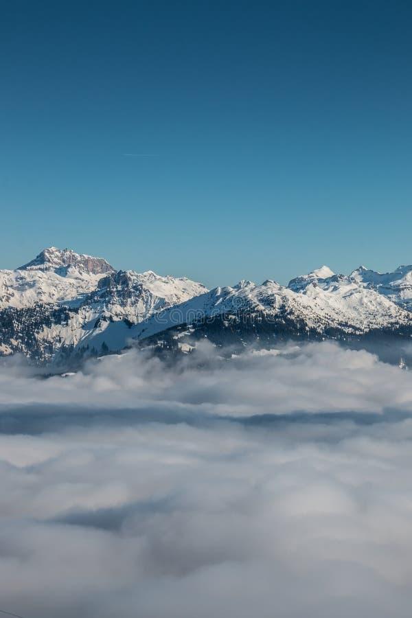 Nieve en el top de las montañas y de la niebla abajo del valle fotos de archivo libres de regalías