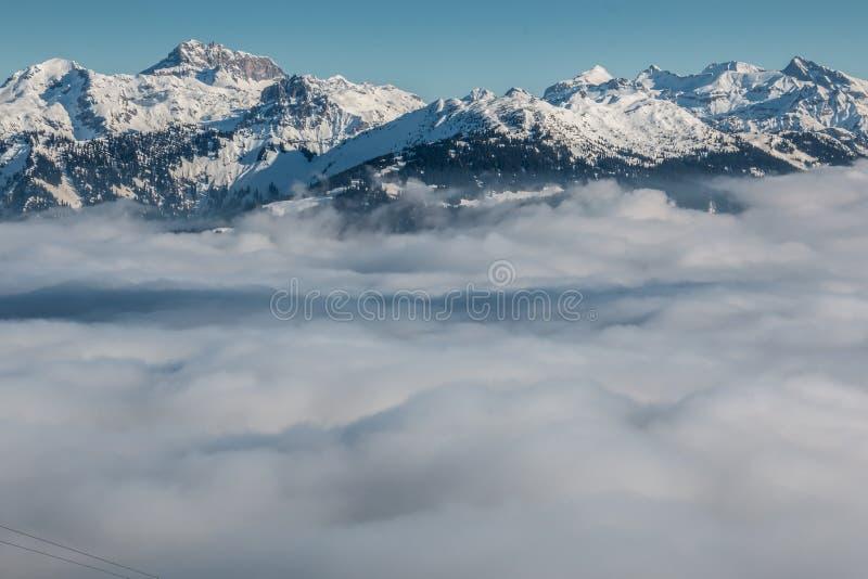 Nieve en el top de las montañas y de la niebla abajo del valle fotografía de archivo