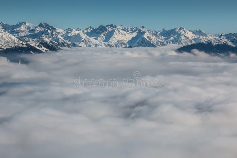 Nieve en el top de las montañas y de la niebla abajo del valle imagenes de archivo