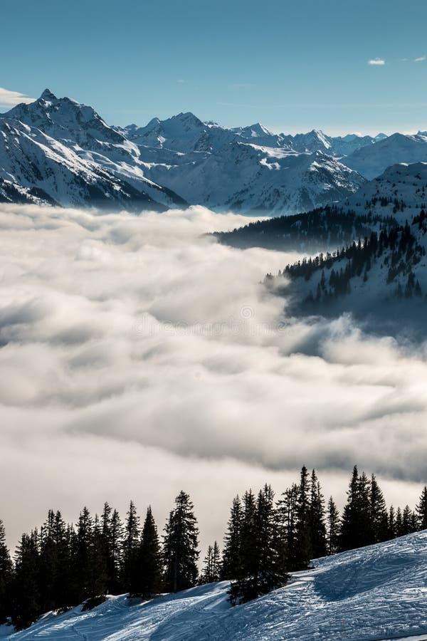 Nieve en el top de las montañas y de la niebla abajo del valle fotos de archivo