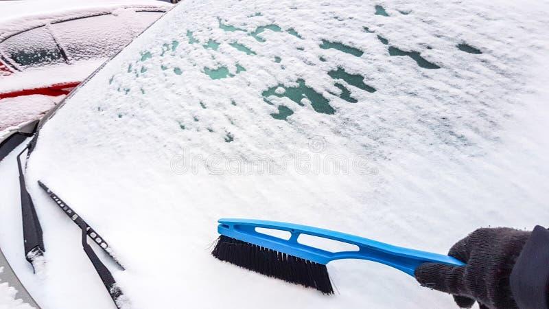 Nieve en la eliminación de la ventanilla del coche foto de archivo
