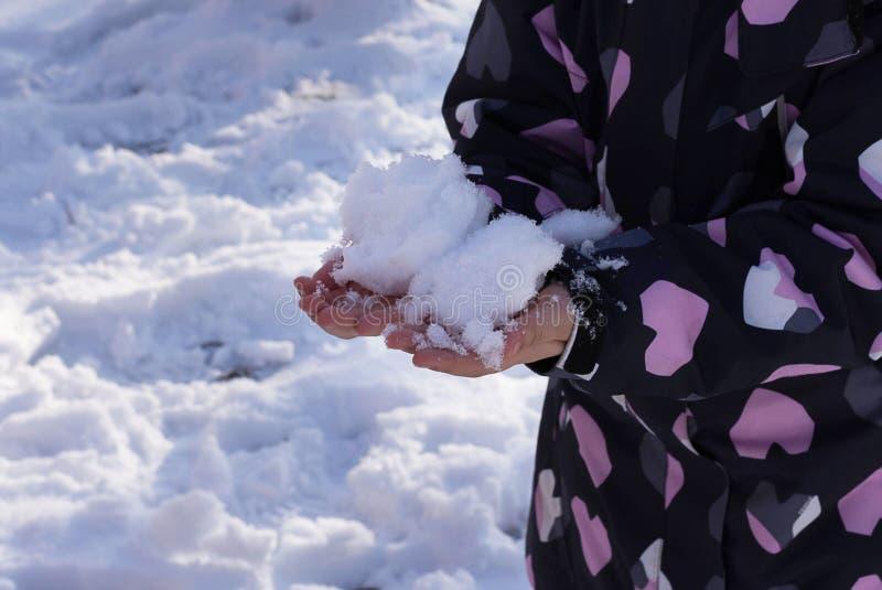 Nieve en la mano del niño Fondo del invierno fotografía de archivo libre de regalías