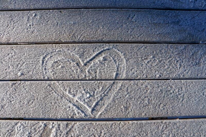 Nieve en la tabla de madera, símbolo del corazón del amor fotos de archivo