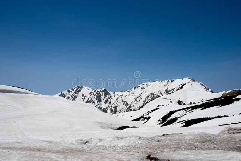 Nieve en las montañas y la opinión de cielo azul en la estación de Murodo de la ruta alpina de Tateyama Kurobe, montañas de Japón fotografía de archivo