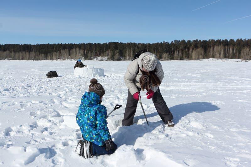 Nieve que asierra de enseñanza del muchacho de la mujer para construir un iglú, Novosibirsk, Rusia imágenes de archivo libres de regalías