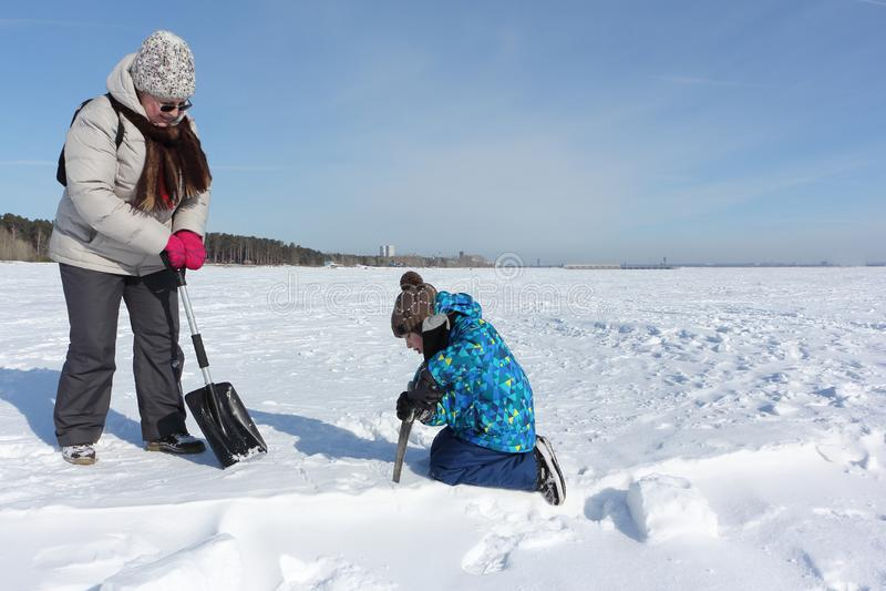 Nieve que asierra de enseñanza del muchacho de la mujer para construir un iglú, Novosibirsk, Rusia fotos de archivo