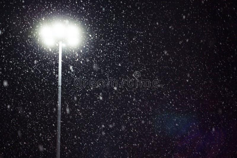 Nieve que cae teniendo en cuenta una linterna imagen de archivo