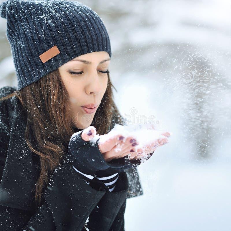 Nieve que sopla de la mujer hermosa joven en invierno foto de archivo