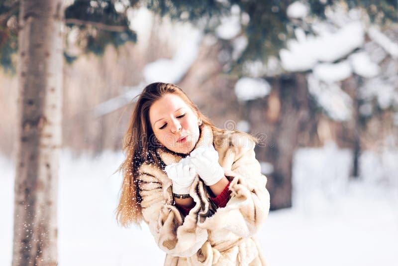 Nieve que sopla de la mujer hermosa joven en invierno fotografía de archivo